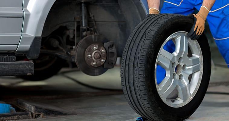 Automechanikas keičia automobilio padangą