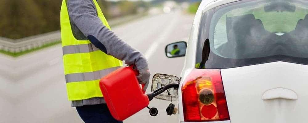 Technines pagalbos darbuotojas pila degalus į automobilio baką