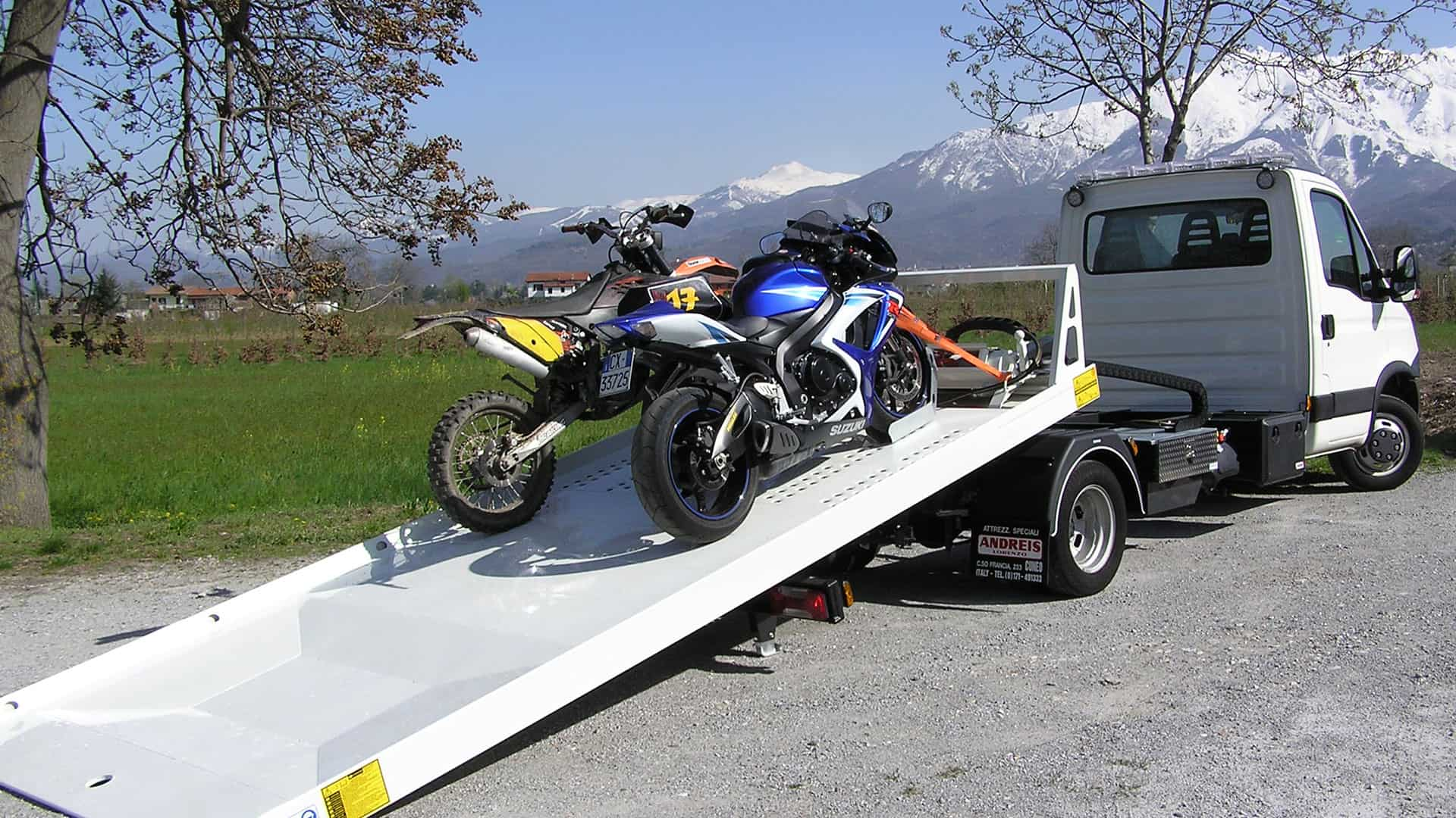 Du motociklai stovi užfiksuoti ant nuleistos tralo platformos